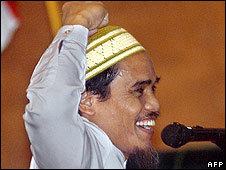 Amrozi cheers after receiving the death sentence at his trial in Bali on 7/08/2003