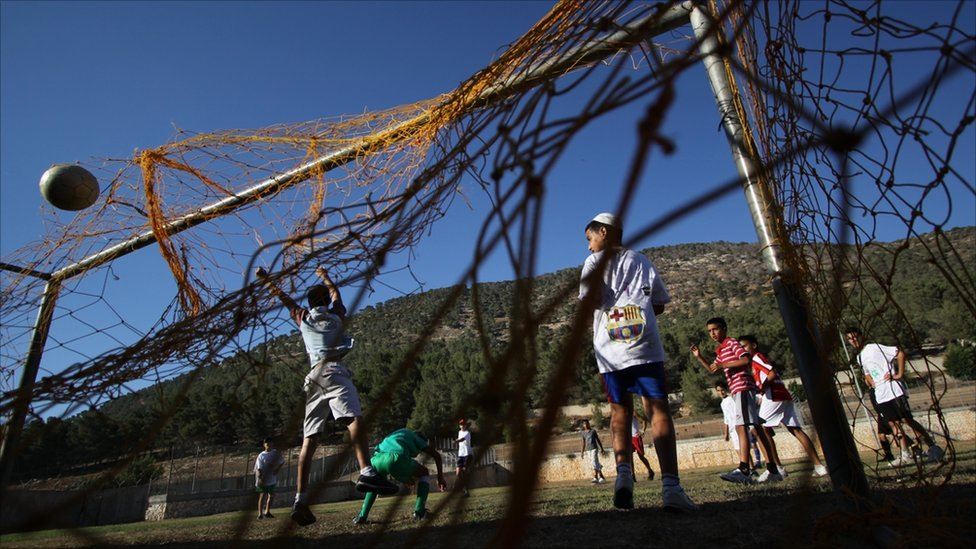 A boys' team play a game of football in Daburiyya, an Arab village in the north of Israel (Image: www.jenswenzel-photography.com)