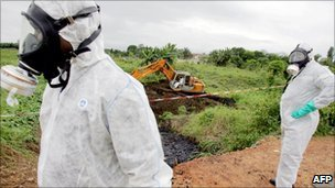 Two civil protection workers pass by a bulldozer clearing a site polluted with toxic waste at the Akouedo district in Abidjan - 19 September 2006