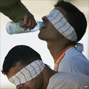 Israeli soldier gives Palestinain prisoner a drink of water