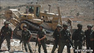 Israeli soldiers guarding a bulldozer