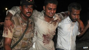 A Pakistani paramilitary soldier and volunteer help an injured man at a bomb blast site in Karachi