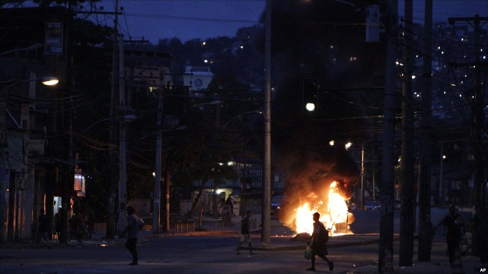 People walk past a vehicle set on fire during riots at Jacarezinho slum in Rio de Janeiro, Brazil.
