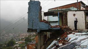 A man looks at a destroyed house in the Catia district in Caracas