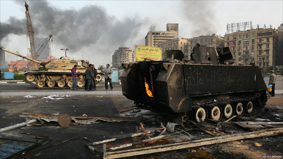 Burned out personnel carrier beside a tank in central Cairo
