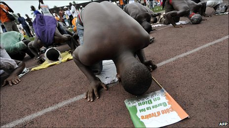 Supporter of Ivory Coast's incumbent President Laurent Gbagbo pray at a political meeting at a stadium in Abidjan on 23 January 2011
