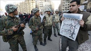 Troops in central Cairo, as man shows newspaper article about members of former regime - photo 13 February