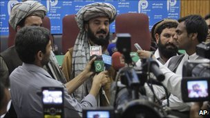 Pakistani tribal elder Malik Jalal, center, flanked by newsmen addresses a news conference to condemn the recent U. S. drone attack in North Waziristan which killed many people, Friday, March 18, 2011 in Peshawar, Pakistan.