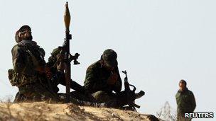 Rebel fighters try to spot coalition planes along Benghazi-Ajdabiya road near Ajdabiya March 25, 2011