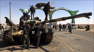 Libyan rebels gather on a destroyed tank in Ajdabiya on 26 March 2011