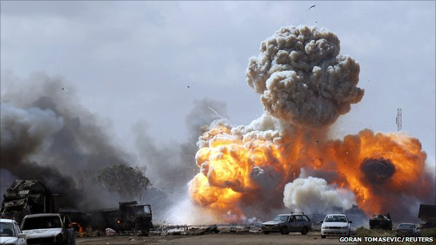 Vehicles belonging to forces loyal to Libyan leader Colonel Gaddafi explode after an air strike by coalition forces, along a road between Benghazi and Ajdabiyah, 20 March 2011