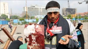 Protester shows blood and suspected bullet cartridges in Tahrir Square, 9 April