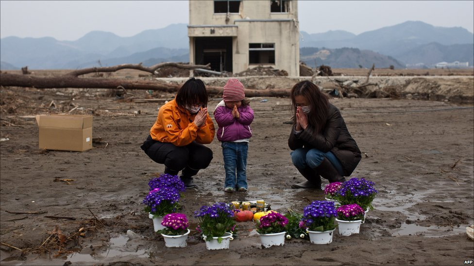 Two-year-old girl and family pray for missing relatives in Ishinomaki, Miyagi prefecture, on 11 April 2011