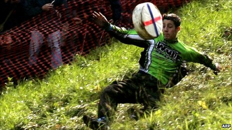 A competitor chases a Double Gloucester cheese down Coopers Hill, Gloucestershire