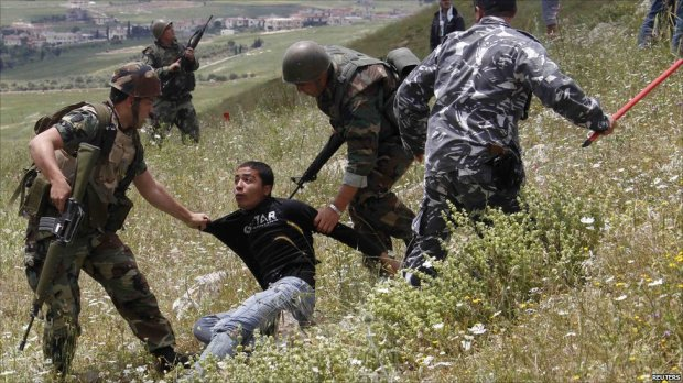 Lebanese troops and Palestinian protesters at Maroun al-Rass, near the Israeli border, 15 May