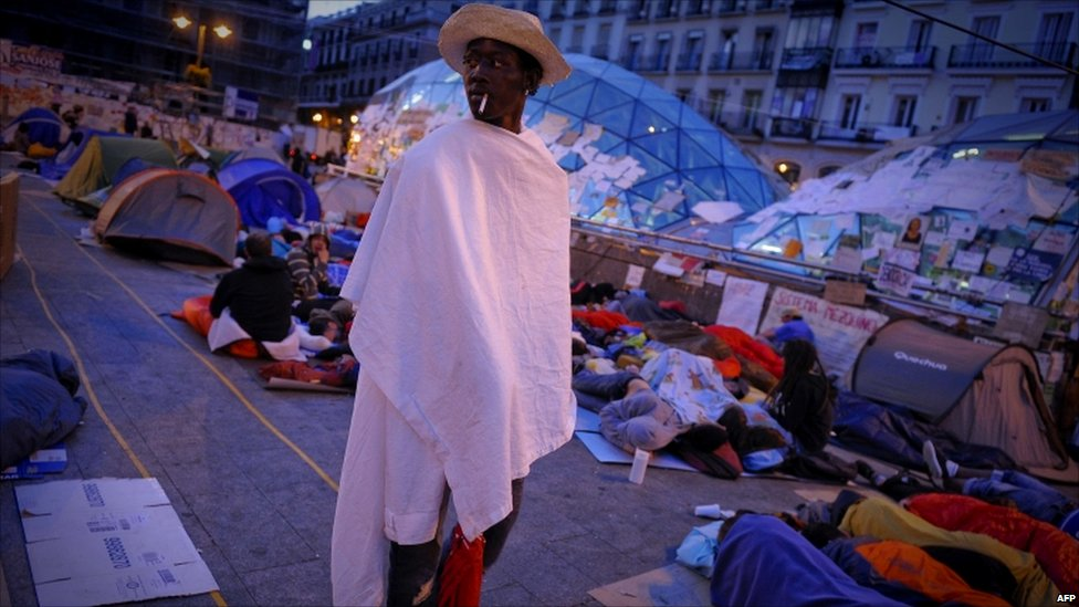 A man stands among protesters occupying the Puerta del Sol square in Madrid, Spain