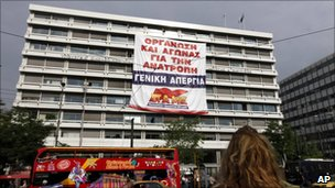 Protesters hung a banner from the Greek finance ministry calling for a general strike