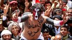 """A Yemeni anti-government protester with the slogan """"Ali escaped"""" painted on his body flashes victory signs in Sanaa"""