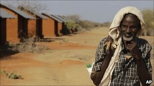 A Somali refugee and goat herder walks past unoccupied refugee housing at Ifo II