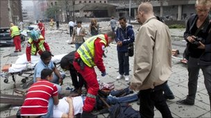 Injured people are treated by medics at the scene of an explosion near the government buildings in Norway's capital Oslo on July 22, 2011