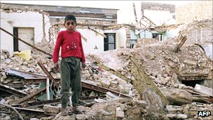 Boy stands in Ahvaz, Iran, on the ruins of his house, destroyed by an Iraqi air raid in 1987