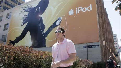 Man with MP3 in front of iPod billboard