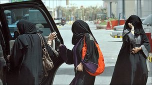 Saudi women get in the back seat of a car