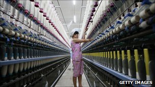 A worker operates machines for making yarn at a textile factory in China's Anhui province