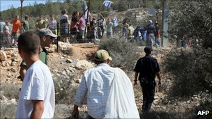 Jewish settlers from Itamar shout from behind a fence as Palestinian farmers from Awarta try to pick olives in October