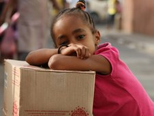 a girl leans on some boxes