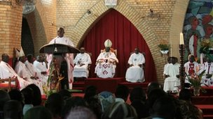 Metropolitan Archbishop Cardinal Mosengo (C-back) listens to Bishop Satendi (L) as he reads a statement, at Notre Dame Cathedral in Kinshasa on January 12 2012