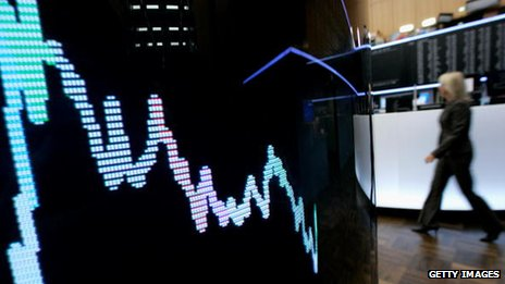 A trader walks past a display screen