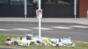 Flowers and messages left beneath Alvechurch School flag