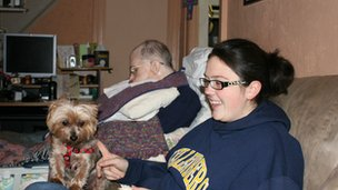 Girl with dog sits on couch while father with Alzheimer's sleeps