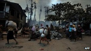 Muslim residents evacuating their houses amid ongoing violence in Burma's Rakhine state