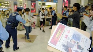 Police officers hand out wanted leaflets of Katsuya Takahashi, the last fugitive of the Aum Shinrikyo cult wanted as a murder suspect in the 1995 sarin nerve gas attack on Tokyo subways, to people at a railway station in Tokyo Friday, 8 June, 2012