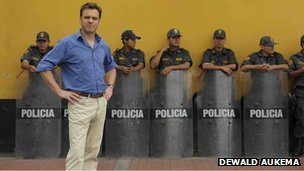 Niall Ferguson standing in front of a row of police officers in Lima, Peru