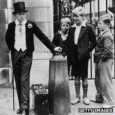 Local boys and boy dressed in Harrow uniform in 1934
