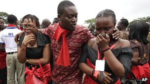 A man consoles two women mourning the death of Ghanaian President John Atta Mills in the capital Accra on 9 August 2012