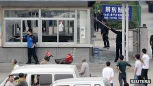 Workers clear up glass from a security office near the entrance to the Foxconn plant
