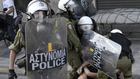 Greek police detain a demonstrator in Athens during the 24hr strike on 18 October 2012