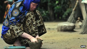 An albino woman in Tanzania moulding a pot from clay in Ukerewe, an island on Lake Victoria, near the town of Mwanza - January 2009