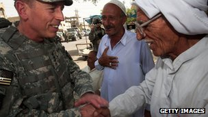 General David Petraeus, commander of US military forces in Iraq, greets Iraqi men at a tea shop in the west Baghdad area of Khadamiyah, 27 June 2007