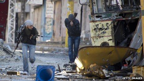 Two rebel fighters dodge sniper fire in Aleppo