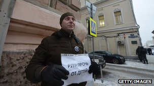 A man holds a poster reading: 'Hands off children!' as he protests against a bill banning Americans from adopting Russian children