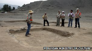 Archaeologists examine the remains of a hearth at the centre of a temple structure