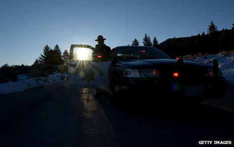 A California Highway Patrol officer guards a roadblock on Highway 38 near the Big Bear Lake, 13 Feb 2013