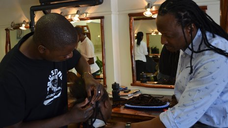 Hair stylist and business man Jabu Stone coaches a stylist on how to insert dreadlock extensions at his salon in Rivonia, Johannesburg