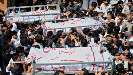 Pakistani Shiite Muslims carry coffins during the funeral procession of bomb blast victims in Karachi on March 4, 2013