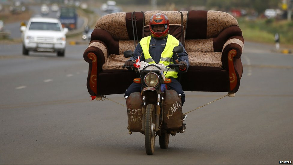 A man carries a sofa on his motorcycle on a highway near Kenya's capital Nairobi on 10 March 2013